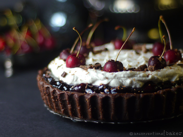 no-bake vegan black forest cake topped with fresh whipped cream cherries and chocolate